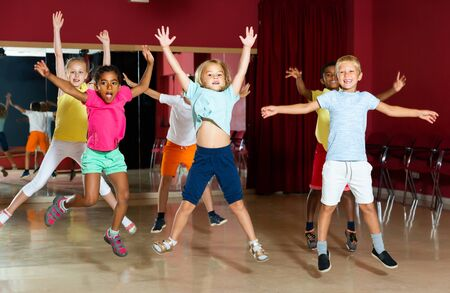 Positive children jumping while studying modern style dance  in class indoors