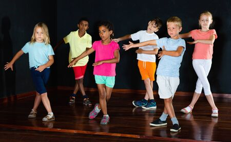 Group of  positive smiling  little boys and beautiful girls having dancing class  in studio  in the evening