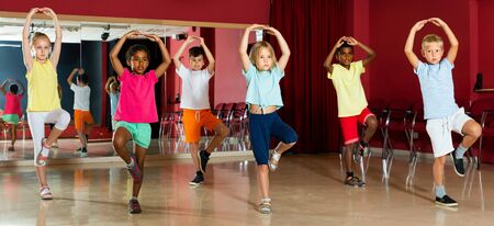 Smiling little boys and beautiful girls having dancing class and hands up in class Stok Fotoğraf