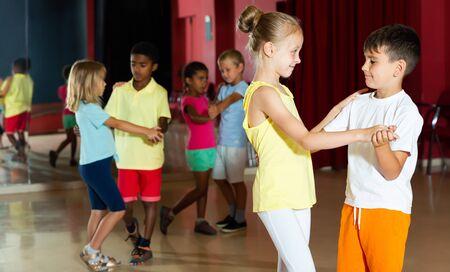 Group of happy children dancing salsa dance in modern studio Stockfoto