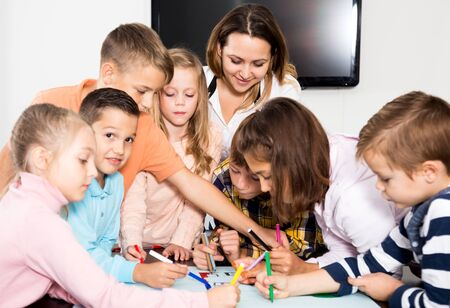 Glad team of elementary age children and female teacher drawing on one sheet Stockfoto