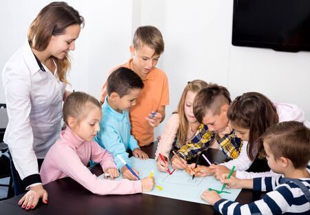 Team of elementary age children  drawing on one sheet Stockfoto