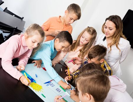 Smiling team of elementary age children and female teacher drawing on one sheet
