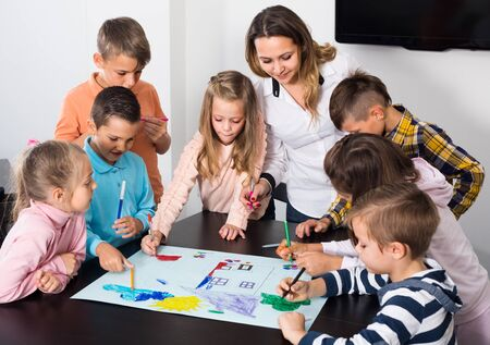 teacher and elementary age children drawing together one picture Stockfoto