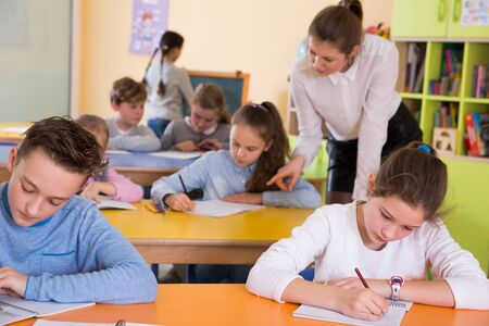Young female teacher and pupils working in classroom at elementary school Imagens