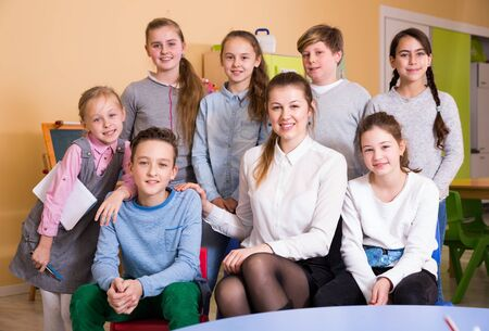 Portrait of friendly smiling group of pupils with female teacher sitting in schoolroom