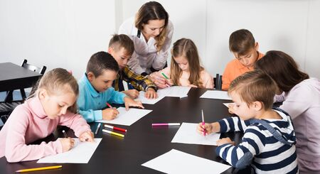 Smiling young boys and girls with teacher drawing in classroom