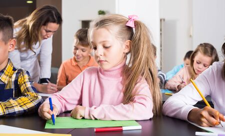 Little children with positive teacher drawing in classroom on the lesson
