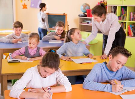 Friendly teacher woman helping children during lesson in a schoolroom