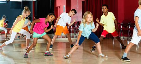 Positive happy  children studying modern style dance  in class indoors