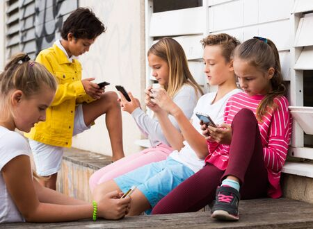 Cheerful children are chatting on their smartphone on walking.