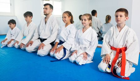 Happy children enjoying their trainings with coach at karate class