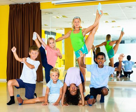 Happy glad  cheerful tweens posing with young female coach during dance training in modern dance school