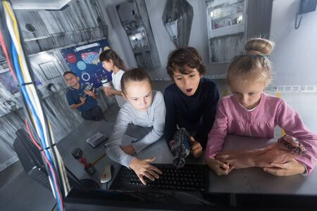 Group of smiling kids are concentrating on finding a way out of mysterious bunker 版權商用圖片