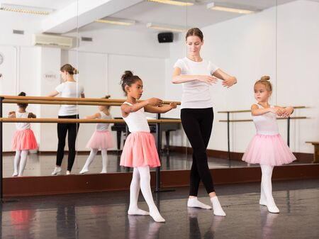 Two little girls practicing choreographic elements in ballet hall