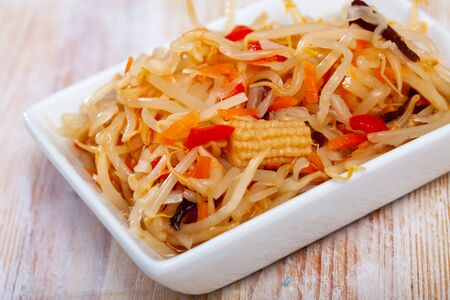 Pickled Chinese style vegetable salad from cabbage, bean sprouts, carrot and corn cobs served on white plate. Concept of vegetarian food