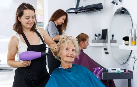 Skillful hairdresser drying hair of elderly female client with blow dryer in modern barbershop