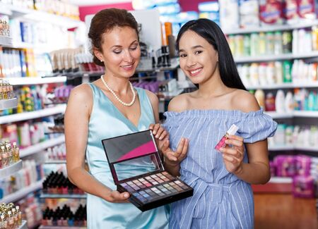 Adult mother and daughter looking eyeshadows in cosmetics shop