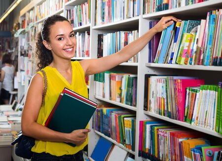 portrait of smiling young brunette woman picking textbooks for school in book shop