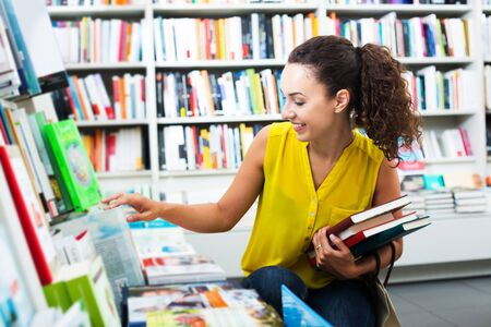 Portrait of cheerful young woman choosing textbooks for school in book shop