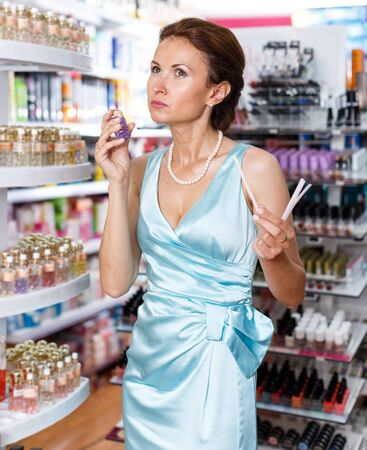Smiling woman customer smelling perfume testers in cosmetic shop Standard-Bild
