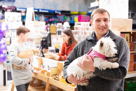 Portrait of positive male visitor with west highland terrier dog in petstore