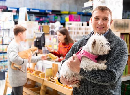 Cheerful friendly smiling positive  man with dog near the cash desk in a pet store 版權商用圖片