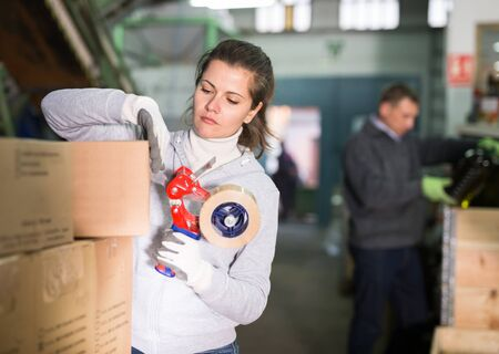 Female employee working at warehouse on artisanal olive oil factory, preparing carton boxes for delivery on market, sealing with sticky tape