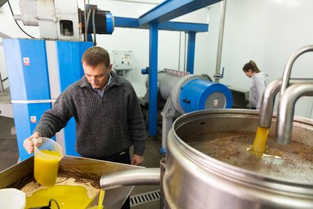Confident male worker controlling quality of olive oil of traditional cold pressing on artisanal olive oil factory