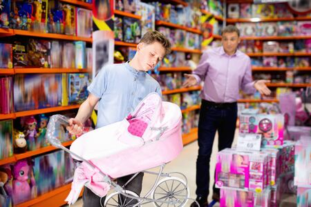 Glad cheerful smiling teen boy choosing pink stroller for dolls in children toy store with adult man dazedly looking at him