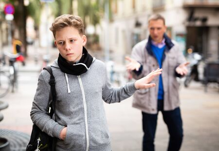 Upset teenage boy making stop gesture to dissatisfied bypasser moralizing him outdoors