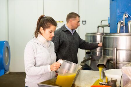 Skilled man and woman engaged in family production of olive oil inspecting first pressing of olives and oil decanting