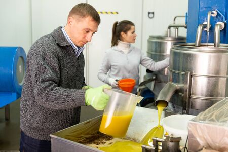 Experienced family couple working on artisan olive oil factory controlling process of oil decanting