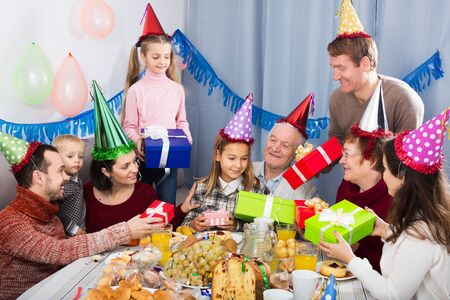 Family members giving presents to little girl during party