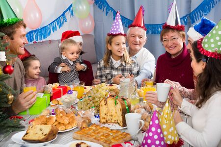 Grandparents 60-70 years old with children are saying toasts to each other during Christmas dinner.