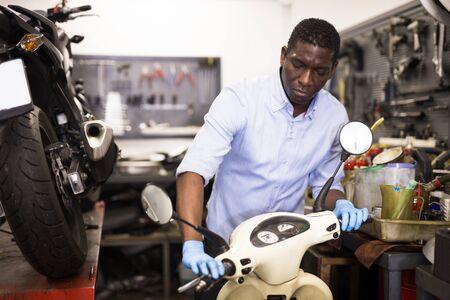 Confident man worker repairing motorcycle in workshop