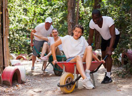 Men drive their girls in garden wheelbarrows. Funny amusement park amusement park Imagens