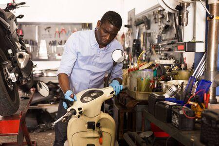 Male afro american worker repairing scooter in motorcycle workshop