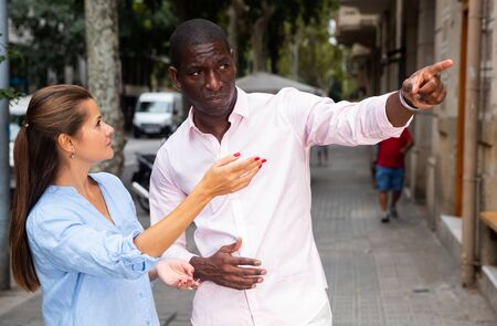 Young woman looking for right address in foreign city, asking friendly African man to show way Stock Photo