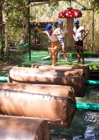 Team of friends overcomes an obstacle course in an amusement park