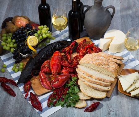 Appetizing smoked sturgeon with lobster, crayfishes, bread, cheese, fruits and wine on wooden surface