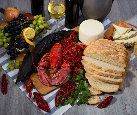 Still life with cooking marine products, wine and cheese on table