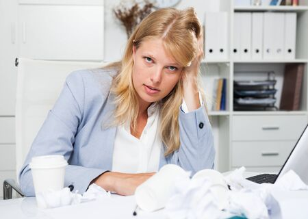 Exhausted of hard work business lady sitting in office among papers
