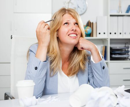 Frustrated business woman sitting among papers and feeling tired after unproductive work