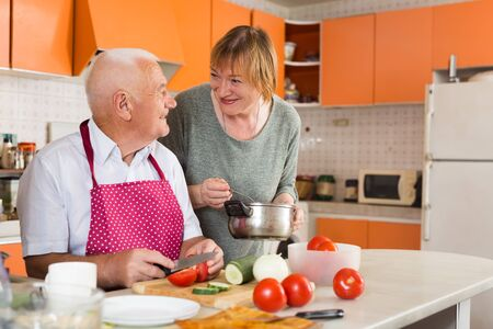 Cheerful senior couple enjoying time together at home, cooking vegetarian lunch in comfy kitchen