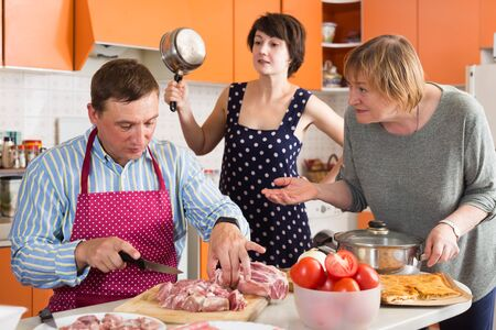 Senior and adult women scolding man cutting meat on wooden board in kitchen