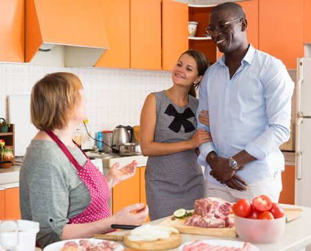 Woman introducing her boyfriend her mother in kitchen Stock Photo