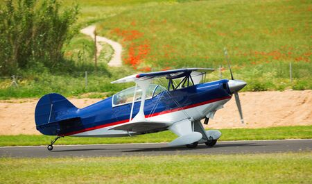 Sport airplane taking up from runway on airfield on summer day Reklamní fotografie