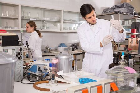 Adult male chemist working in laboratory, analyzing liquid samples in test flasks