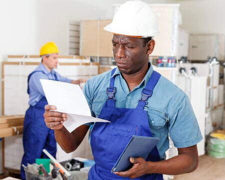 Professional African-American builder standing at indoors building site in hardhat, reading document
